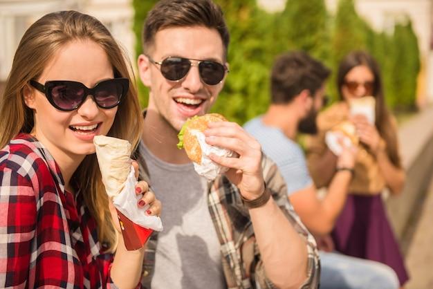 Ludzie w okularach jedzą fast foody.