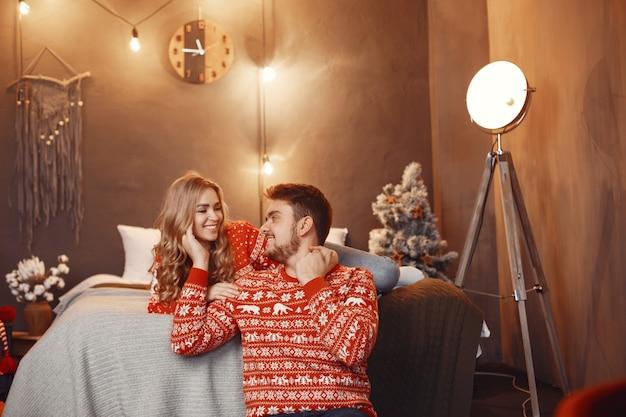 Ludzie w ozdób choinkowych. mężczyzna i kobieta w czerwonym swetrze.