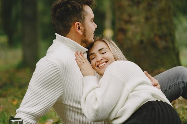 Ludzie w parku. kobieta w brązowym płaszczu. mężczyzna w białym swetrze. para na pikniku.
