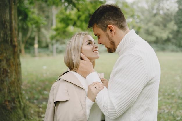 Ludzie w parku. kobieta w brązowym płaszczu. mężczyzna w białym swetrze.