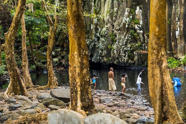 Ludzie w pobliżu wodospadu rochester na wyspie mauritius, wodospad w dżungli na tropikalnej wyspie mauritius.