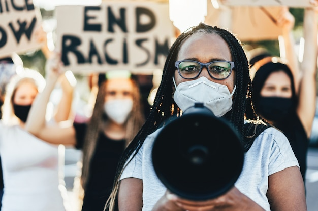 Ludzie w różnym wieku i rasy protestują na ulicy o równe prawa - demonstranci w maskach podczas kampanii walki z czarnymi istotami - koncentracja na twarzy kobiety