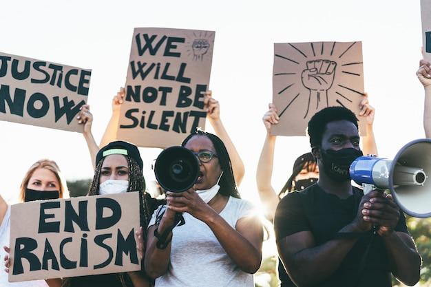 Ludzie w różnym wieku i rasy protestują na ulicy o równe prawa - demonstranci w maskach podczas kampanii walki z czarnymi istotami -