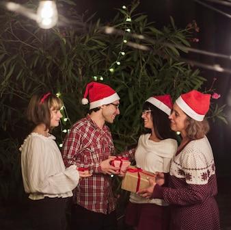 Ludzie w Santa kapelusze wymieniają prezenty