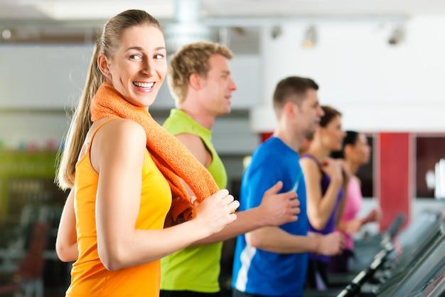 Ludzie w siłowni na bieżni