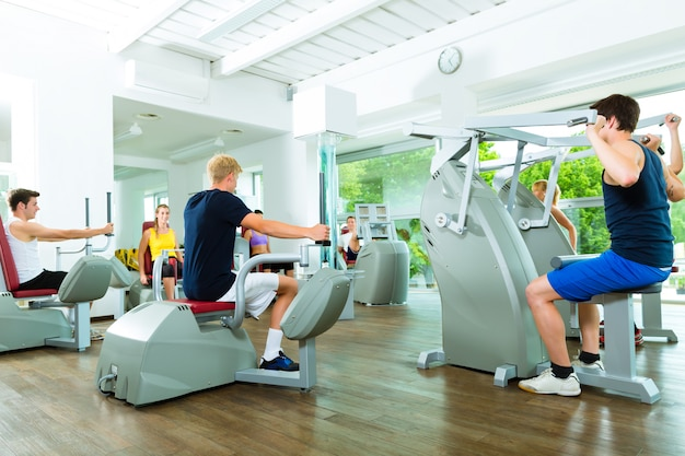 Ludzie w siłowni sportowej na maszynach