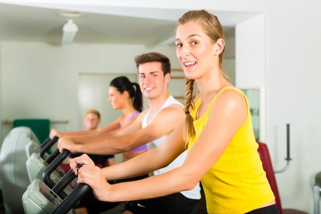 Ludzie w siłowni sportowej na maszynie fitness