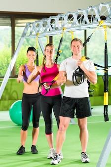 Ludzie w siłowni sportowej na trenerze zawieszenia