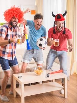 Ludzie w strojach oglądają piłkę nożną i kibicują drużynie.