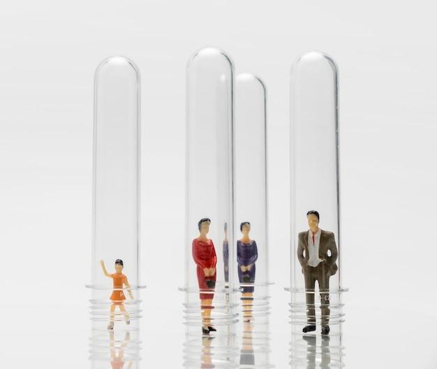 Ludzie w szklanych probówkach podczas pandemii koronawirusa dla ochrony