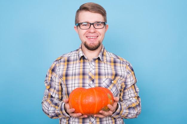 Ludzie wakacje i jesień koncepcja przystojny mężczyzna trzyma dynie na niebieskim tle