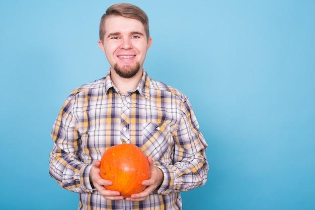 Ludzie wakacje i koncepcja halloween młody szczęśliwy mężczyzna trzyma dynię na niebieskim tle