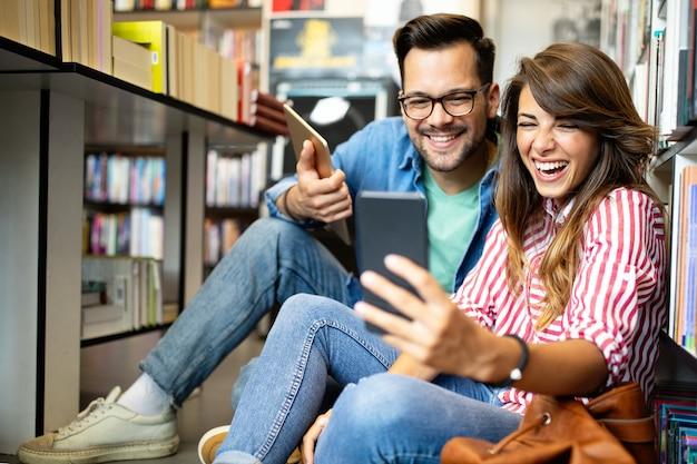 Ludzie, wiedza, edukacja koncepcja szkoły studiów. grupa szczęśliwych studentów czytających książki i przygotowujących się do egzaminu w bibliotece