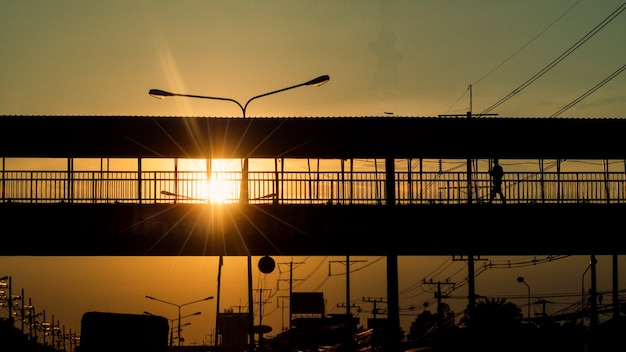 Ludzie wracają po pracy do domu. pomysł na życie w wielkim mieście w czasie zachodu słońca na moście. sylwetki samochodów i pieszych przechodzących przez most nad mostem na tle zachodu słońca