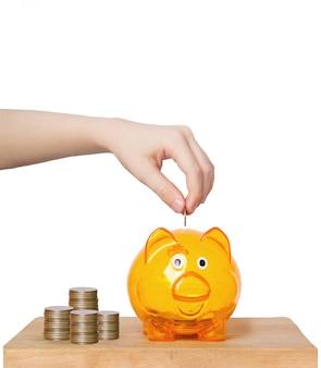 Ludzie wręczają kładzenie monetę w prosiątko banku.