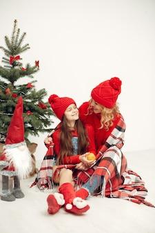 Ludzie wynagradzający święta. matka bawi się z córką. rodzina odpoczywa w świątecznym pokoju. dziecko w czerwonym swetrze.