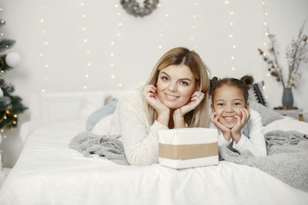 Ludzie wynagradzający święta. matka bawi się z córką. rodzina odpoczywa w świątecznym pokoju. dziecko w swetrze sweter.