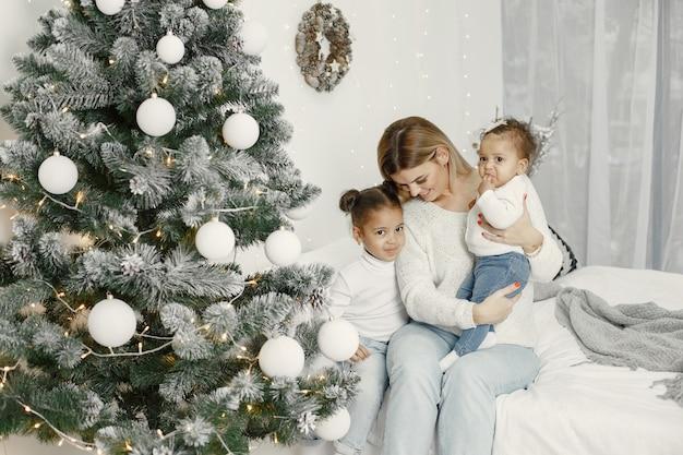 Ludzie wynagradzający święta. matka bawi się z córkami. rodzina odpoczywa w świątecznym pokoju. dziecko w swetrze sweter.