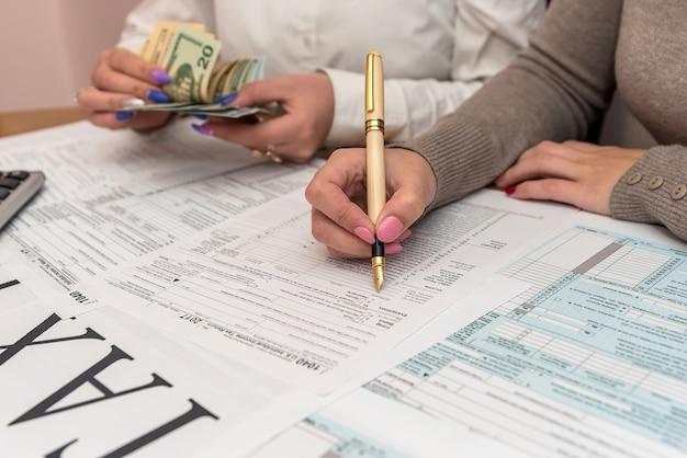 Ludzie wypełniają formularz 1040 i liczą banknoty dolarowe