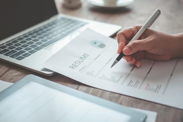 Ludzie wypełniają swoje cv na formularzu podania o pracę, aby ubiegać się o pracę w firmie.