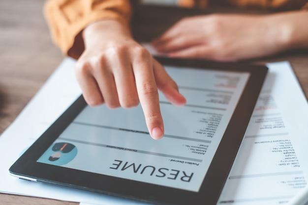 Ludzie wypełniają swoje osobiste cv na tablecie, aby aplikować online o pracę.