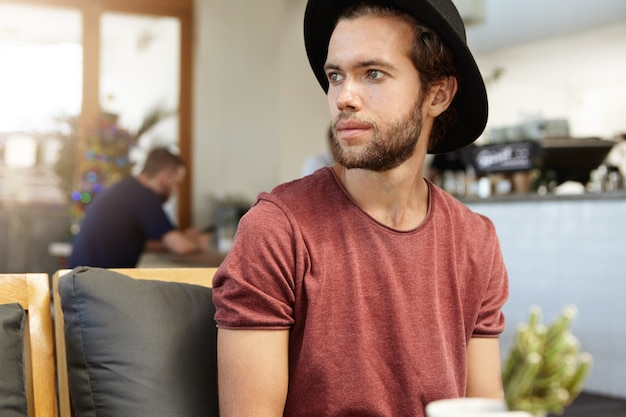 Ludzie, wypoczynek i koncepcja nowoczesnego stylu życia. portret przystojny młody człowiek z grubą brodą na sobie czarny kapelusz po odpoczynku w pomieszczeniu sam