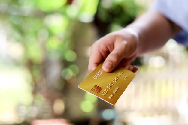 Ludzie wysyłają czerwone karty kredytowe, kartami kredytowymi można płacić za towary i usługi w sklepach detalicznych, restauracjach lub podczas zakupów online. koncepcja korzystania z karty kredytowej.