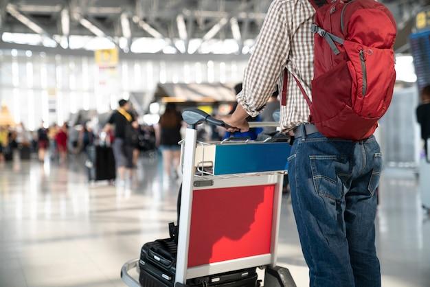Ludzie z bagażem w wózku na lotnisku.
