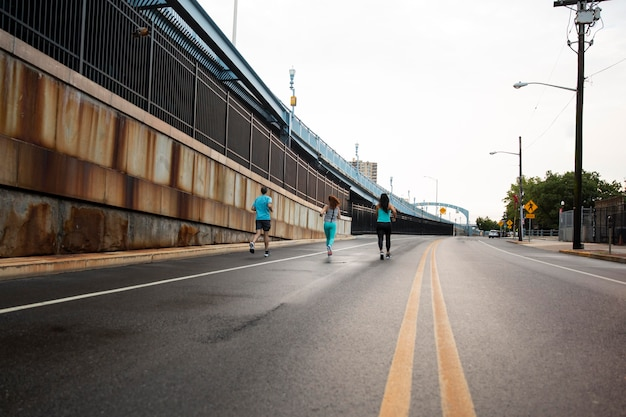 Ludzie z długiego strzału biegnący po ulicy