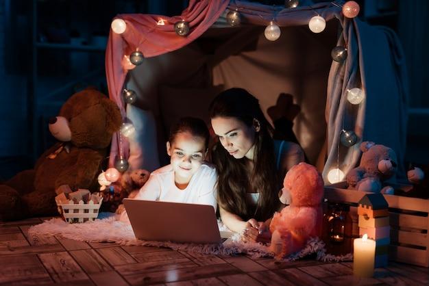 Ludzie z laptopem w domu z poduszkami późno w nocy w domu.