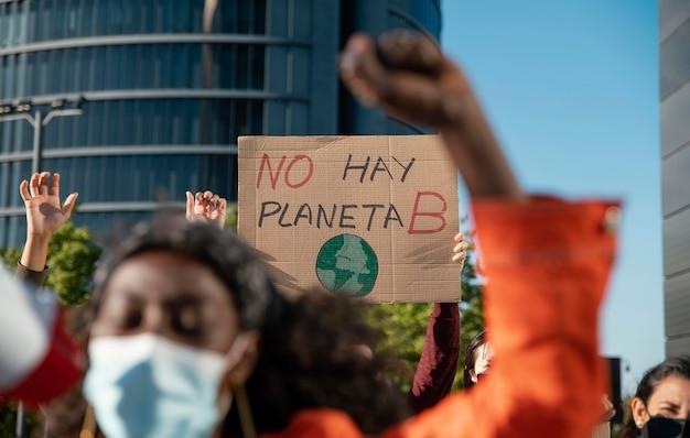 Ludzie z maskami i tabliczkami na zewnątrz