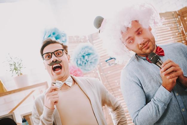 Ludzie z muszką śpiewają piosenki karaoke na imprezie.