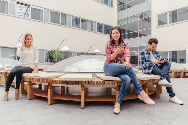Ludzie z smartfonami na ławce
