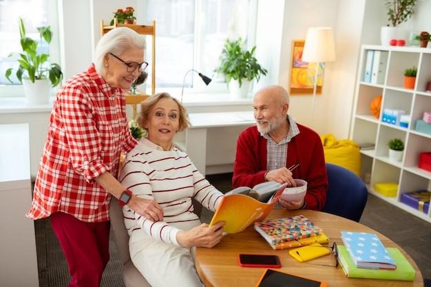 Ludzie z tym samym hobby. szczęśliwa miła kobieta opowiadająca o swojej książce podczas wizyty w klubie czytelniczym