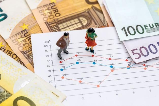 Ludzie zajmujący się małymi zabawkami omawiają wykres i euro