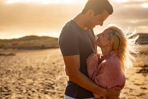 Ludzie zakochani i złoty zachód słońca na zewnątrz - para mężczyzna i kobieta przytulają się i patrzą na siebie z plażą w tle - koncepcja ochrony i życia razem na zawsze