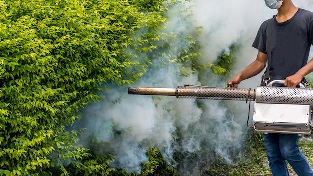 Ludzie zamgławiający spray ddt zabijają komary w celu zwalczania malarii, zapalenia mózgu, dengi i ziki