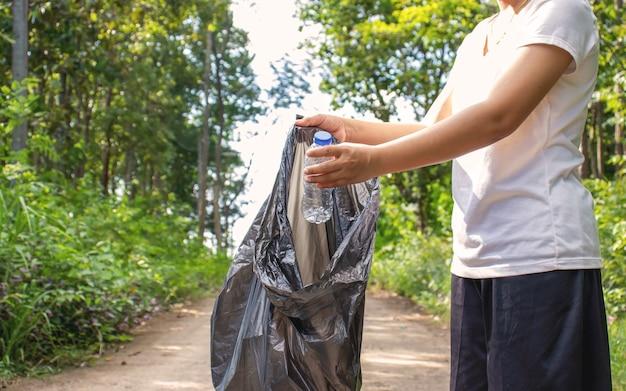 Ludzie zbierają plastikowe butelki do ponownego użycia i ochrony środowiska.
