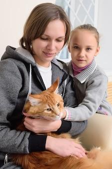 Ludzie ze swoimi zwierzętami czekają na badania lekarskie w klinice weterynaryjnej.
