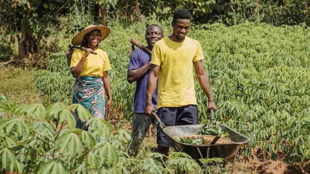 Ludzie ze wsi pchający taczki