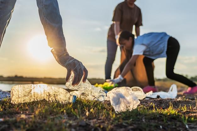Ludzie zgłaszają się na ochotnika do przechowywania śmieci plastikowej butelki do czarnej torby w parku w pobliżu rzeki o zachodzie słońca