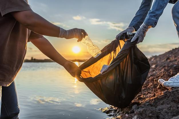 Ludzie zgłaszają się na ochotnika do przechowywania śmieci plastikowej butelki w czarnej torbie na rzece w zachodzie słońca