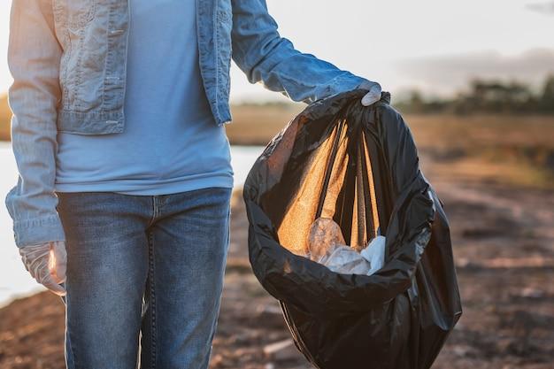 Ludzie zgłaszają się na ochotnika do przechowywania śmieci plastikowych i szklanych butelek do czarnej torby w parku rzeki o zachodzie słońca