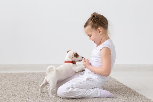 Ludzie, zwierzęta domowe i koncepcja zwierząt - mała dziewczynka siedzi na podłodze na białym tle i trzyma szczeniaka jack russell terrier.