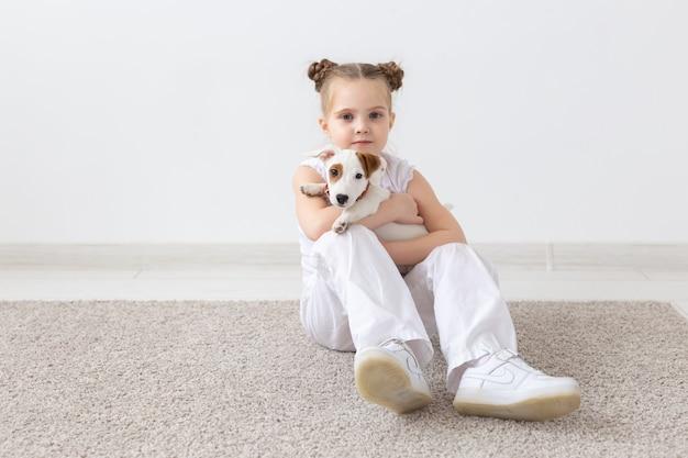 Ludzie zwierzęta i koncepcja zwierząt mała dziewczynka siedzi na podłodze nad białą ścianą i trzyma