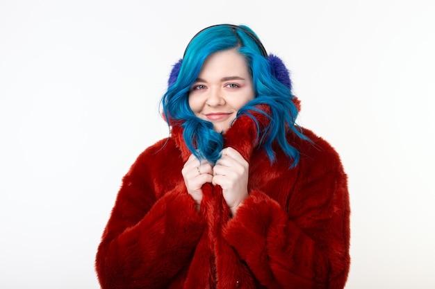 Ludzie, zwierzęta ochronne i koncepcja mody - piękna dziewczyna o niebieskich włosach ubrana w czerwony ciepły płaszcz
