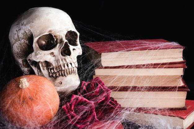 Ludzka czaszka z różami i pajęczyna