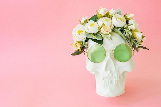 Ludzka czaszka z zielonymi okularami i kwiatami na białym tle