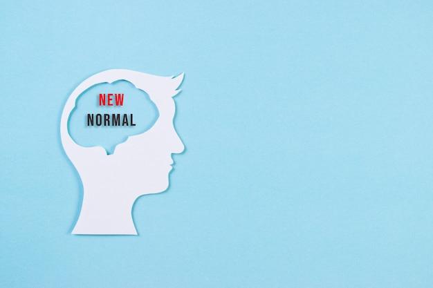 Ludzka głowa wykonana z papieru wyciętego z tekstem. nowa normalna koncepcja po pandemii covida-19. skopiuj miejsce