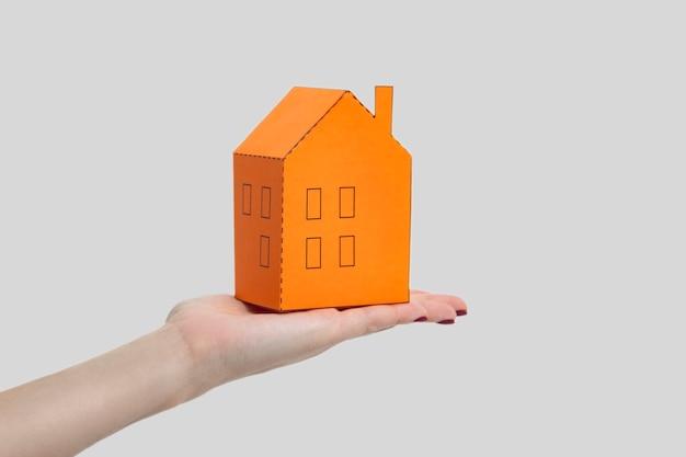 Ludzka kobieta ręka trzyma i pokazuje model domu pomarańczowy papier. kryty strzał studio, na białym tle na szarym tle.